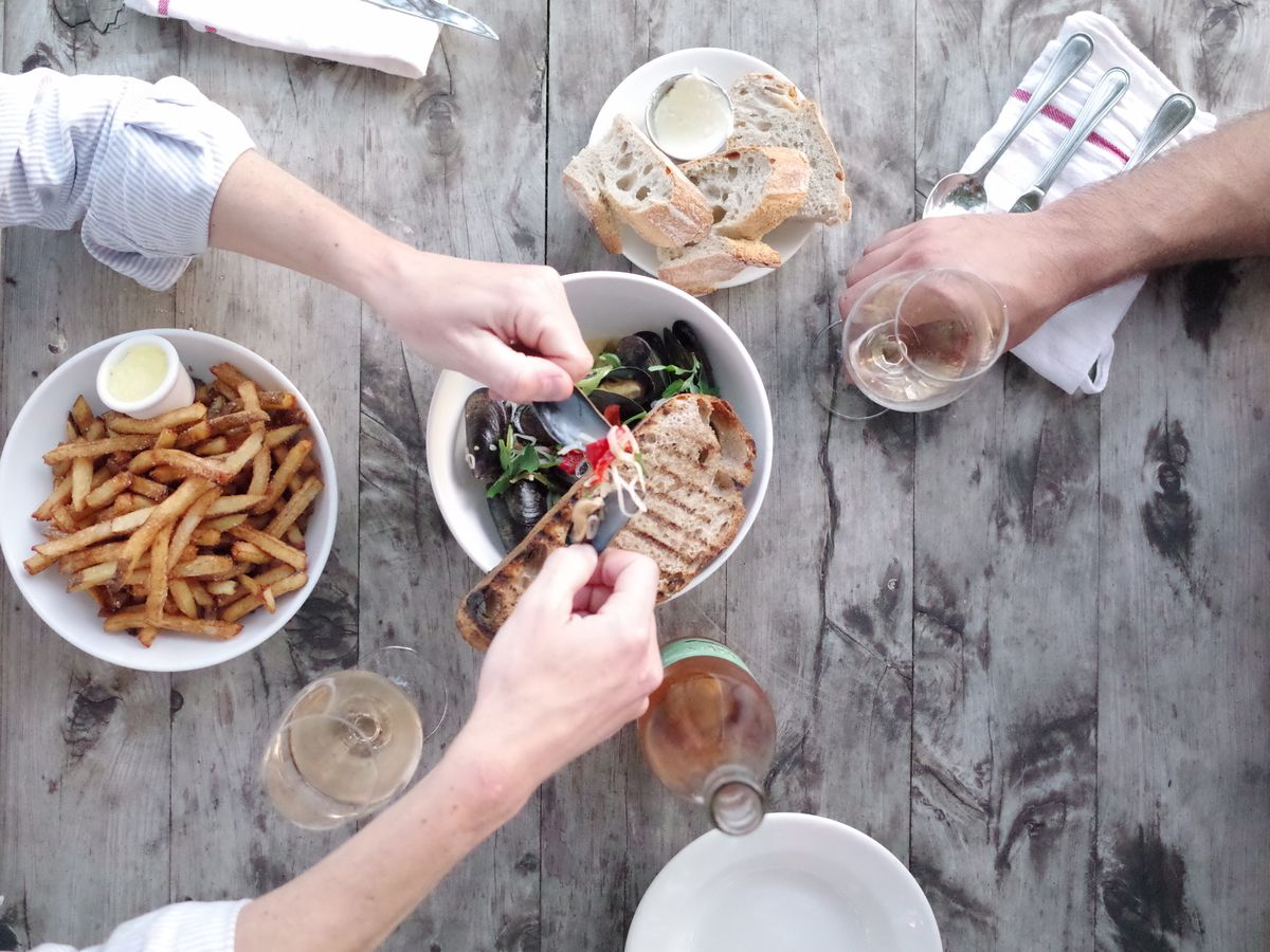 Hands reaching for food in dishes on a table