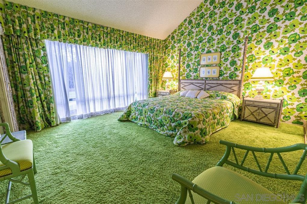 A floral green pattern covers the walls and bedding of a bedroom, which also has a solid green carpet.