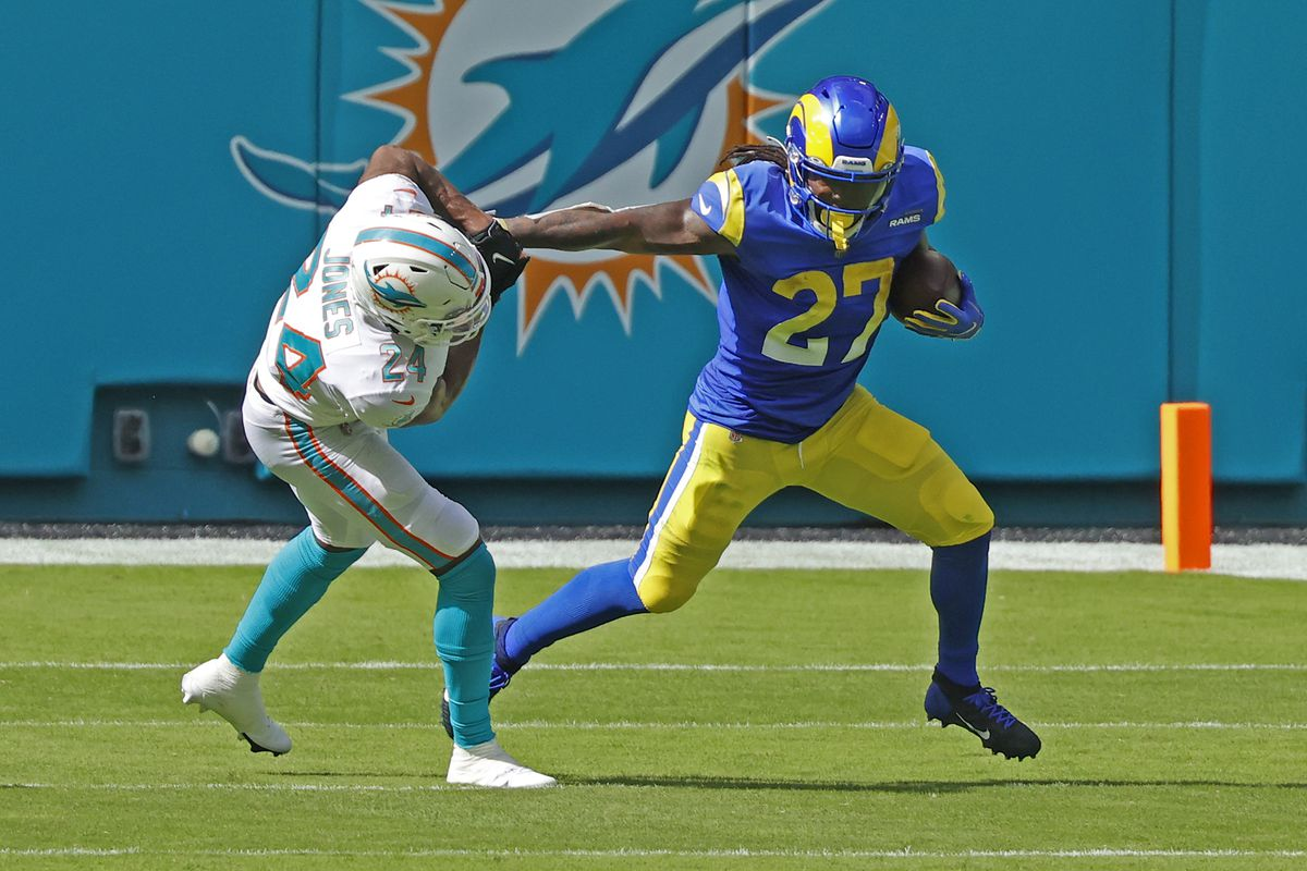 Darrell Henderson Jr. #27 of the Los Angeles Rams stiff arms Byron Jones #24 of the Miami Dolphins as he runs with the ball during an NFL game on November 1, 2020 at Hard Rock Stadium in Miami Gardens, Florida.