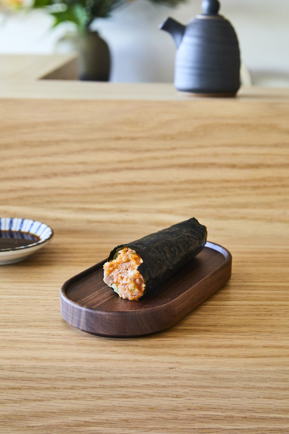 A yellowtail hand roll in a nori on a wooden plate.