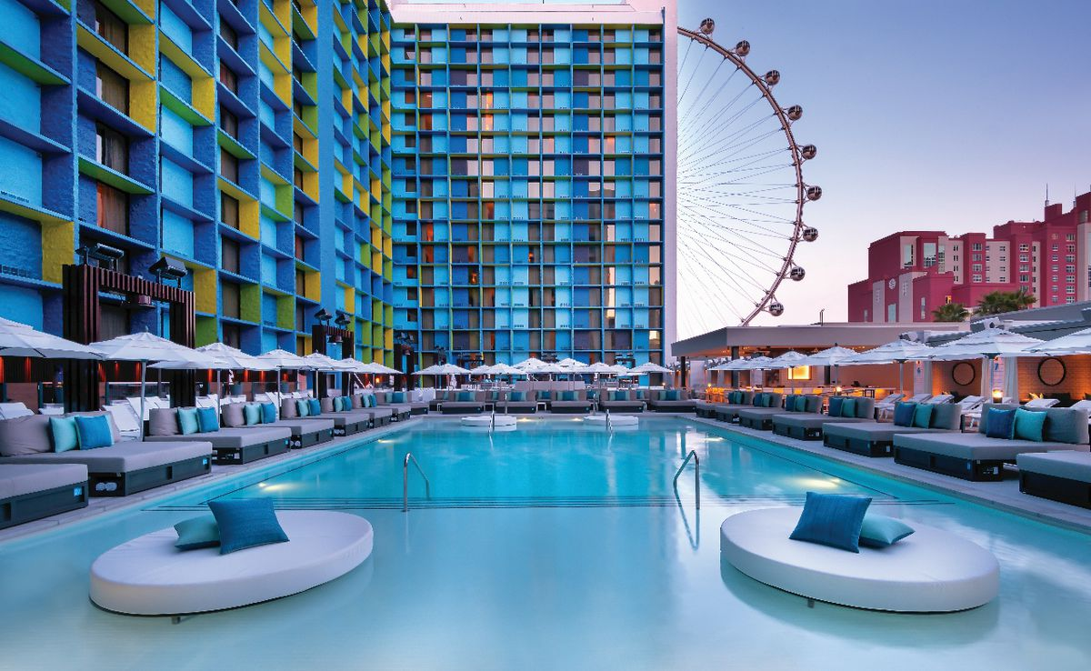 A pool with a hotel and Ferris wheel in the background