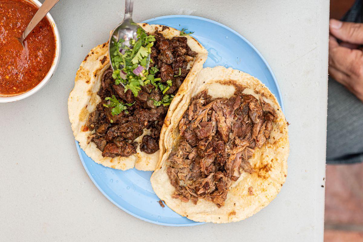 Goat barbacoa and pancita tacos at Barbacoa Los Ramones on a bright blue plate.