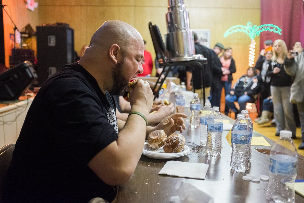 A bald man bites into a paczki at the PLAV Post #10 contest.