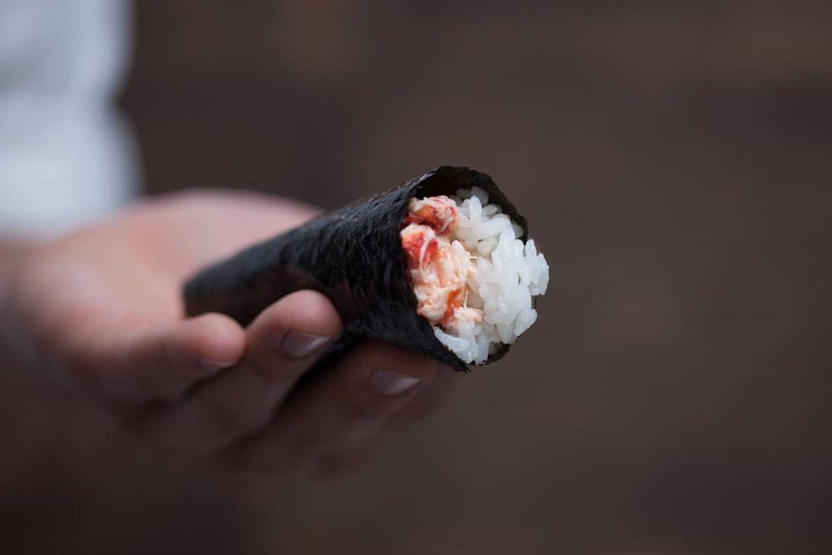 A hand shows off a hand roll of sushi.