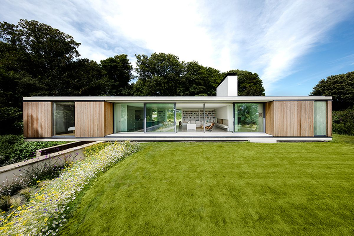 Modern house cantilevers over stone wall in england curbed Modern house architecture wikipedia