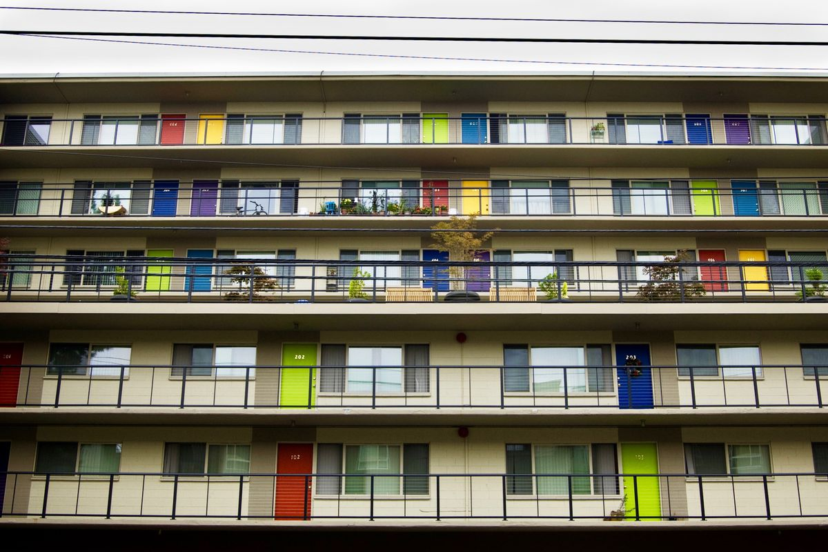 An apartment building with outside entrances to the units and colorful doors—red, yellow, green, blue, and purple.