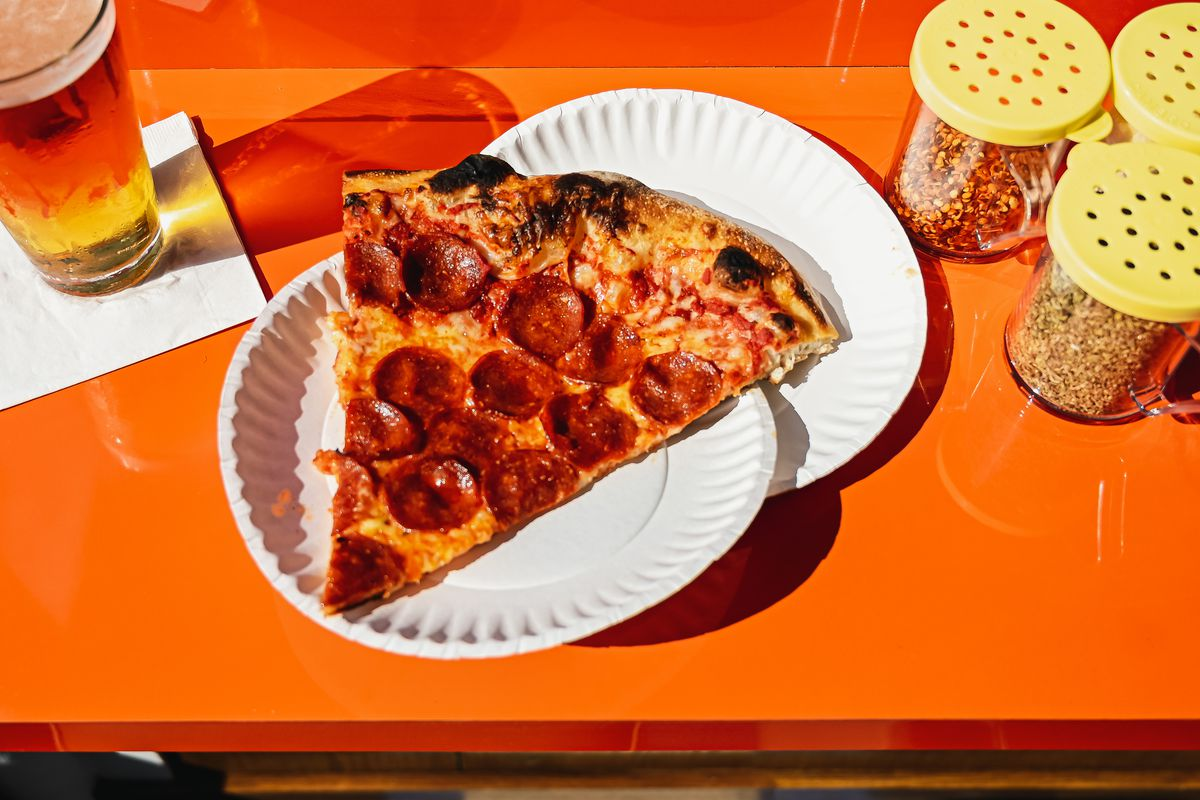 A pepperoni pizza slice on two white paper plates on an orange table with a glass of beer to the left and pizza topping containers to the right