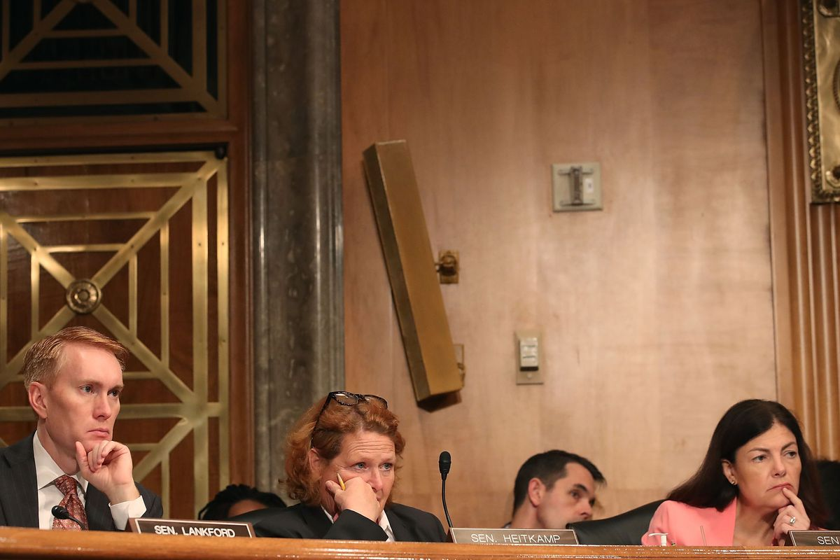 (From left) Sen. James Langford (R-OK), Sen. Heidi Heitkamp (D-ND), and Sen. Kelly Ayotte (R-NH), listen to testimony during a Senate Homeland Security and Governmental Affairs Committee hearing on Capitol Hill.