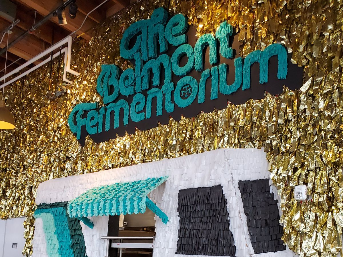 """bright colored golden decor and the words """"The Belmont Fermentorium"""" sit above a food window designed to look like a food truck"""