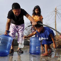 Residents of Tacloban gather to get water, Friday, Nov. 22, 2013.