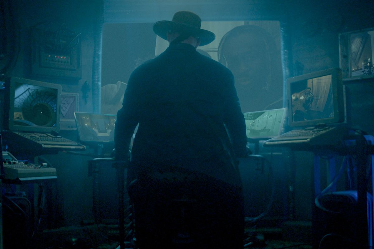 the undertaker at a row of computers, plotting something devious