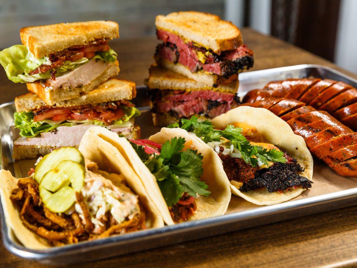 Three tacos, a turkey club, a pasrami sandwich, and sausage on a metal tray