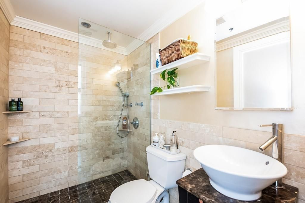 A bathroom with a partially enclosed shower and a basin sink.