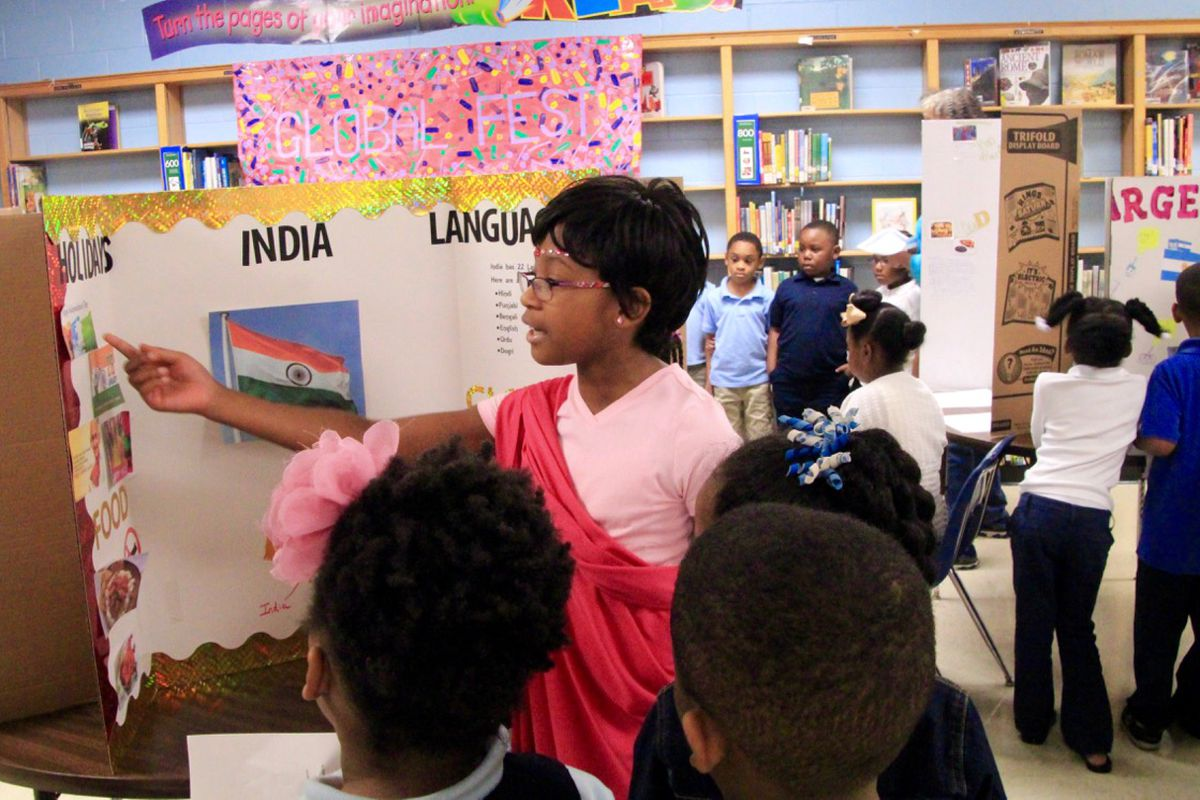 A second-grader teaches younger students about India, a country she studied this year at John P. Freeman Optional School.