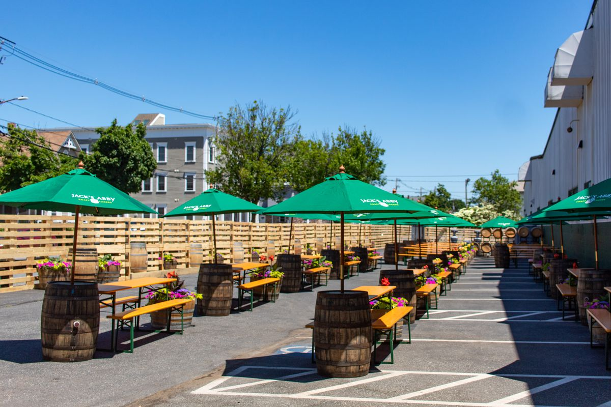 A brewery's beer garden is set up in a parking lot, featuring three neat rows of picnic tables, each with a green umbrella