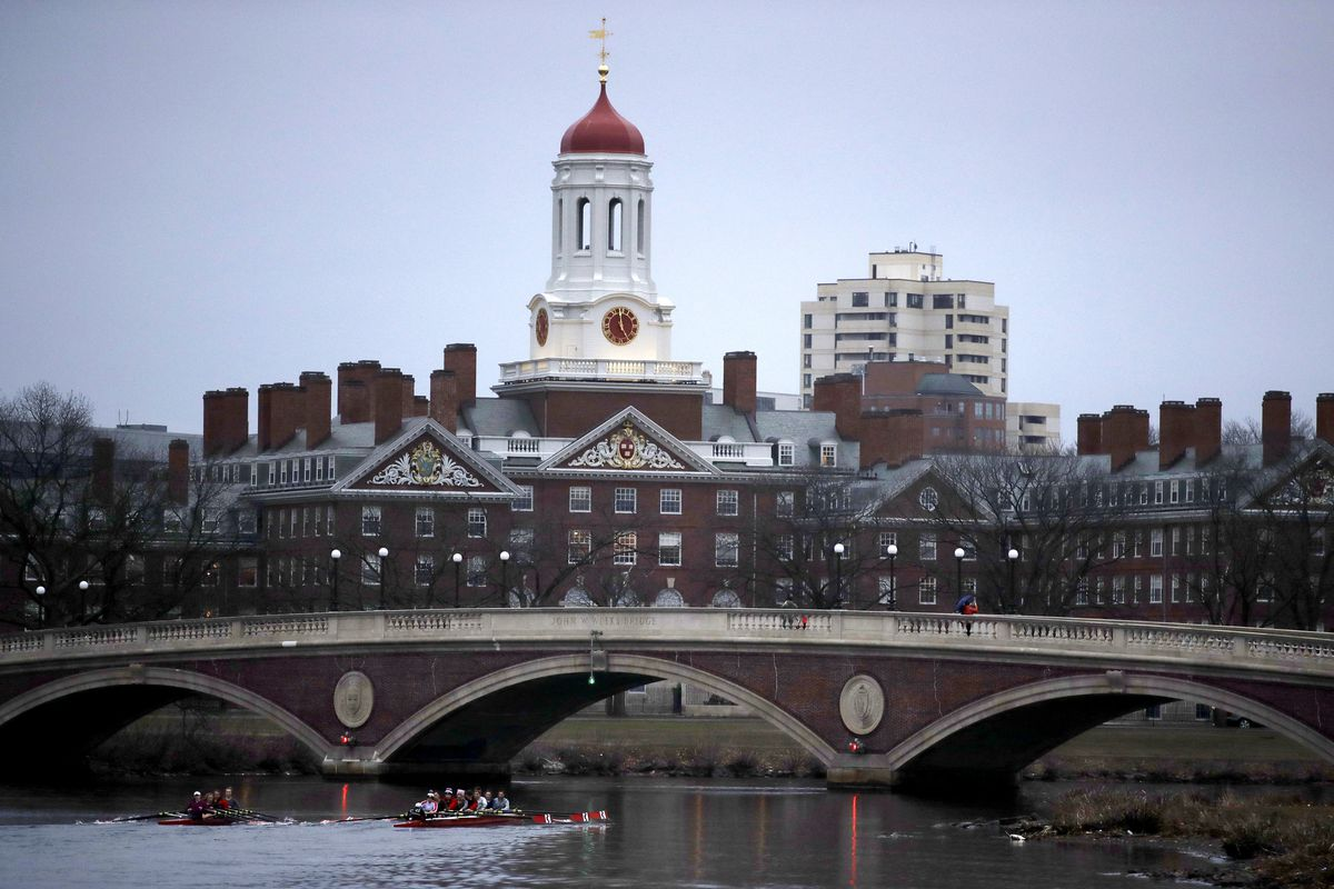 FILE - In this March 7, 2017 file photo, rowers paddle down the Charles River past the campus of Harvard University in Cambridge, Mass. A lawsuit alleging racial discrimination against Asian American applicants in Harvard's admissions process is heading t