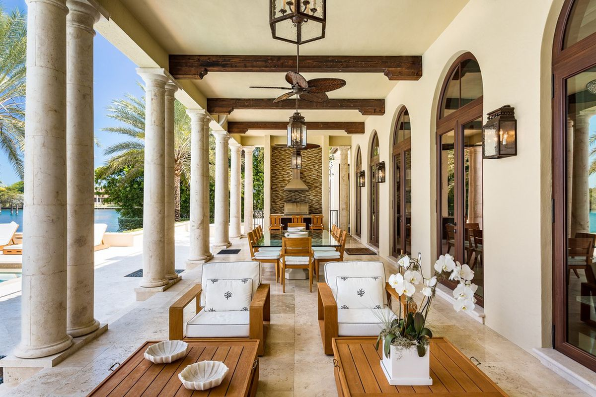 The outdoor entertaining area at a Coral Gables mansoin with a glass dining table, grill, wooden patio furniture in front, and columns to the left separating the dining area and the pool.