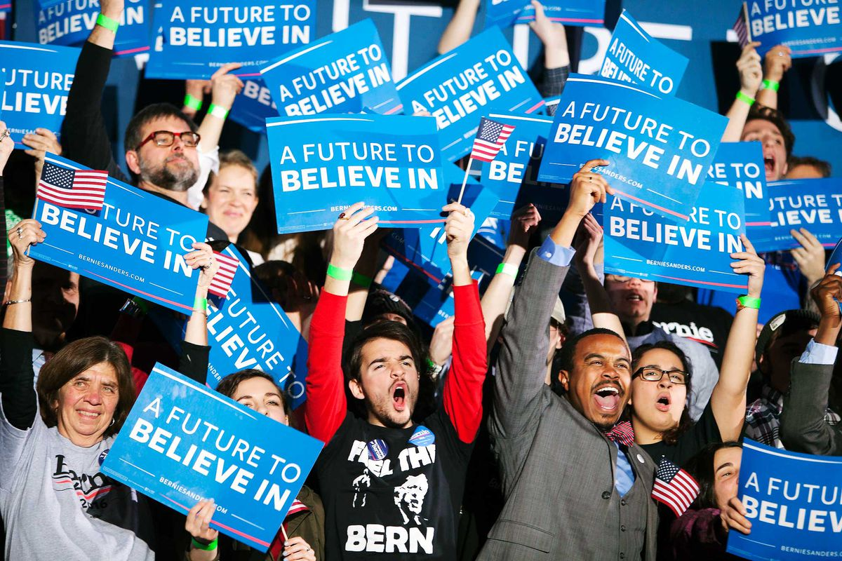 """People cheering and holding signs that read """"A Future To Believe In."""""""