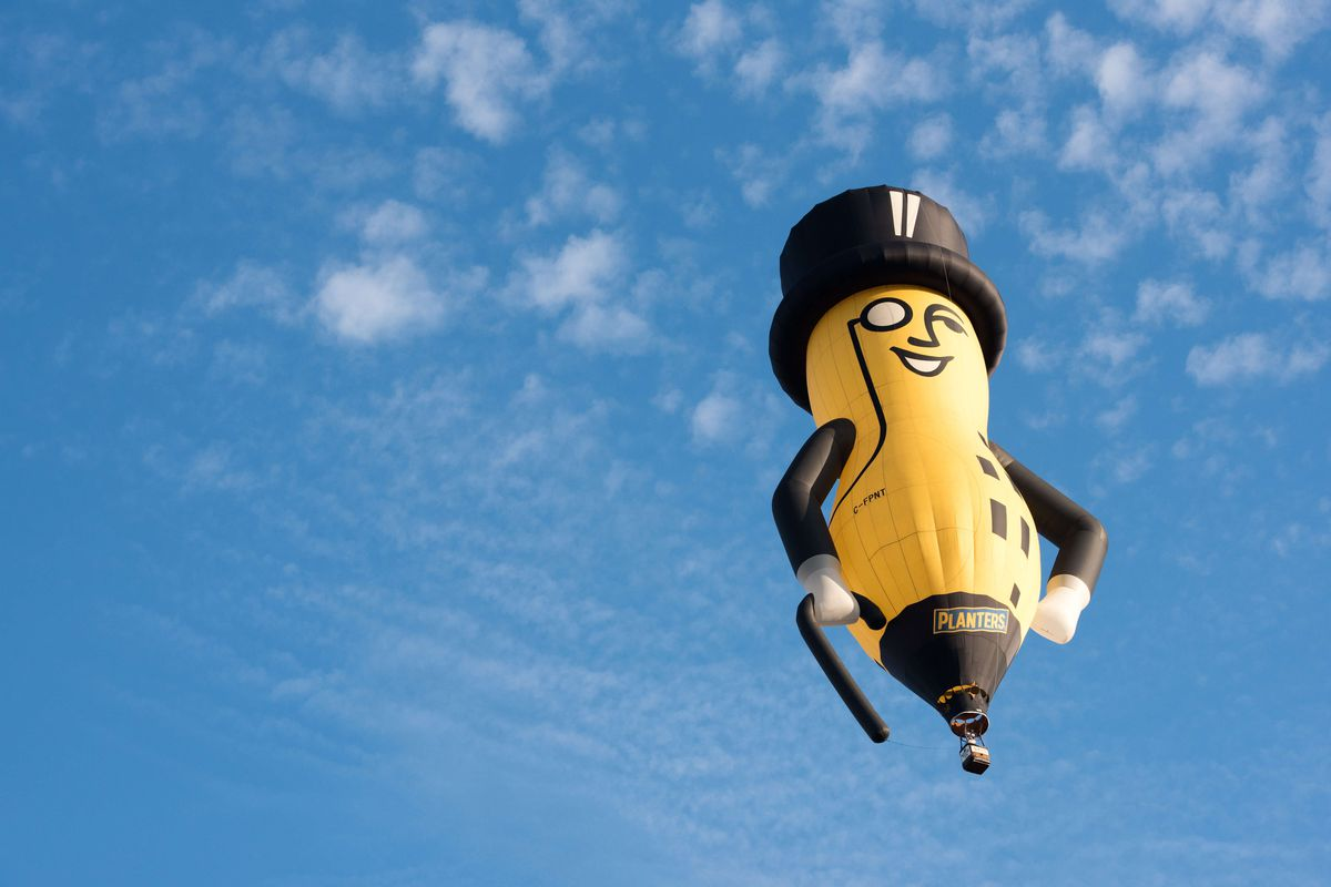 A hot-air balloon in the shape of Mr. Peanut floats across a blue sky scattered with clouds.
