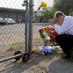 Bob Hoskovec says a prayer as he kneels outside the gate of the Granite Mountain Interagency Hot Shot Crew fire station, Monday, July 1, 2013, in Prescott, Ariz. An out-of-control blaze overtook the elite group of firefighters trained to battle the fiercest wildfires, killing 19 members as they tried to protect themselves from the flames under fire-resistant shields. The disaster Sunday afternoon all but wiped out the 20-member Hotshot fire crew leaving the city's fire department reeling. (AP Photo/Julie Jacobson)