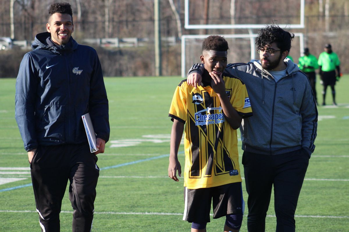Three men on a soccer field. On the far left, a coach is smiling at the camera while holding a binder. On the right, Warshan Hussin has his arm around a player who is wearing a yellow jersey.