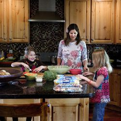 Cherise Udell makes a salad with daughter Sophia, left, and Sophia's friend, Shae Sorenson. Udell wants to teach her children to volunteer in street-level pursuits.