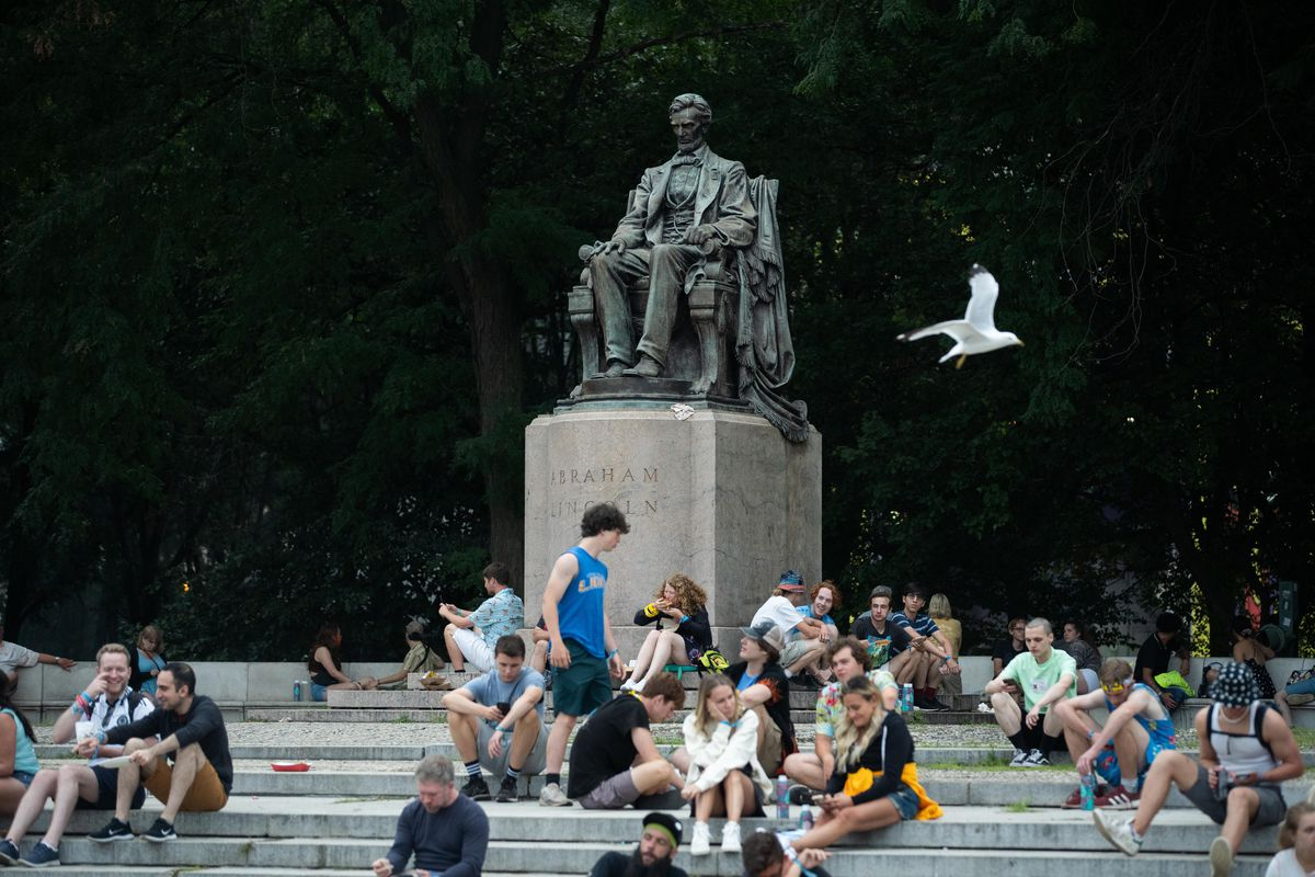 People sit near the Abraham Lincoln statue in Grant Park.