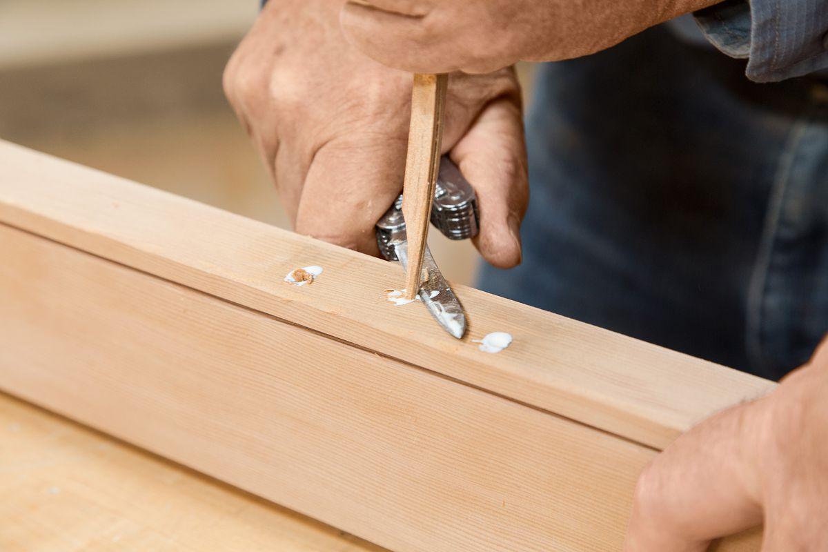 Pessoa tapando buracos na madeira com cola.