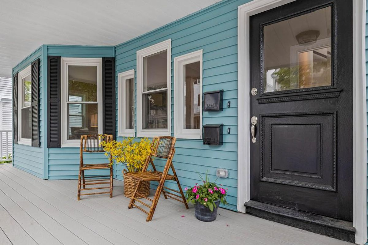 The front porch of a condo building, with a front door and a couple of chairs.