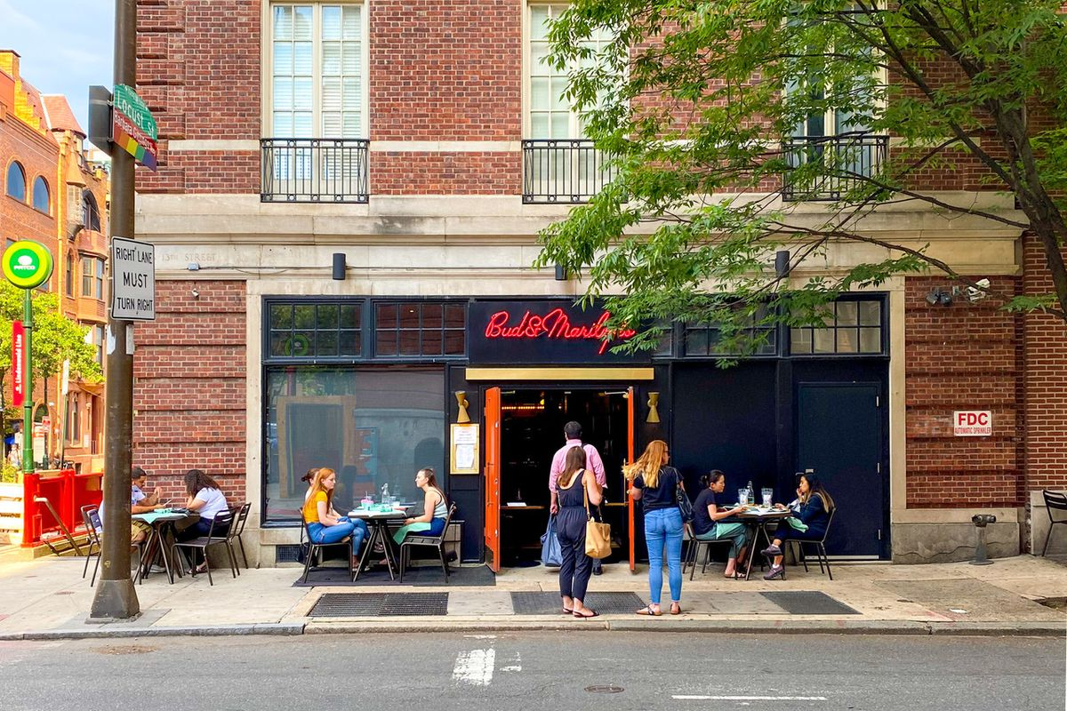 diners eating at sidewalk tables in front of a restaurant with a black and red facade