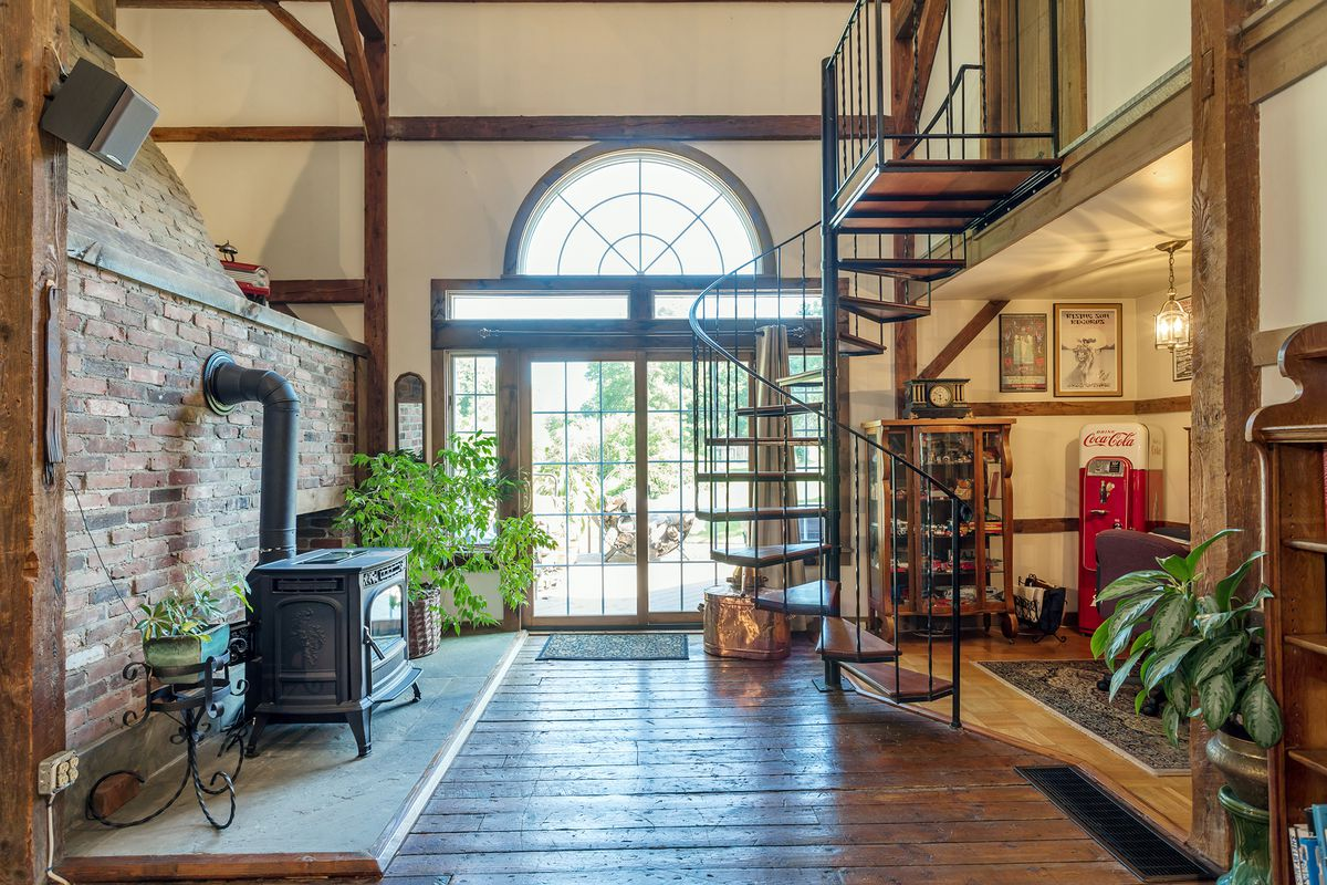 A hallway has a brick wall with old stove and a spiral staircase that leads to the bedrooms.