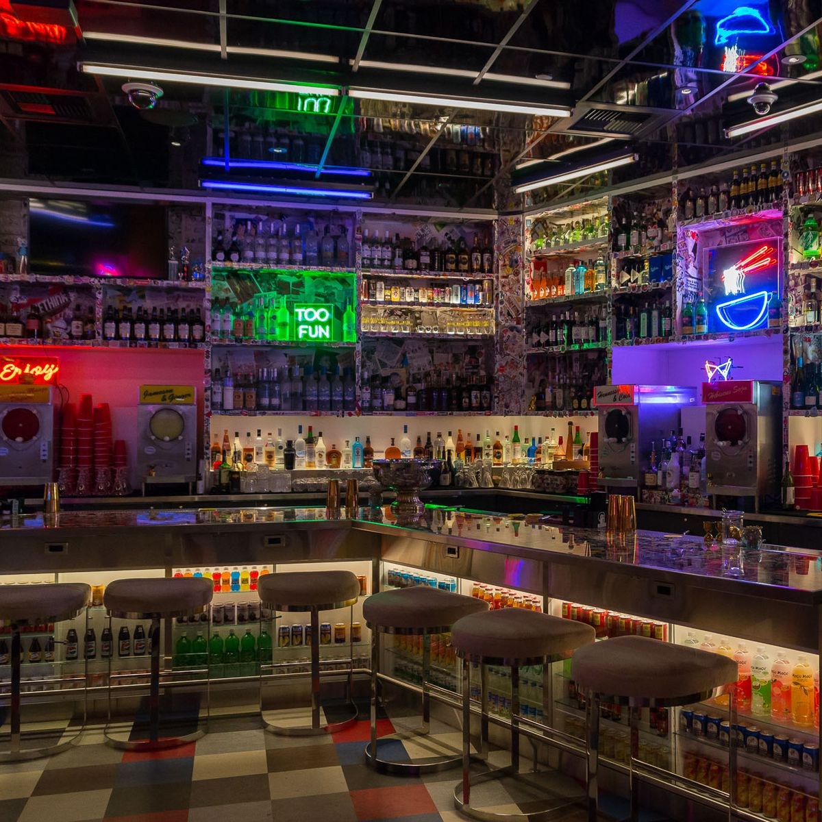 Bar with bar stools and tons of bright neon signs