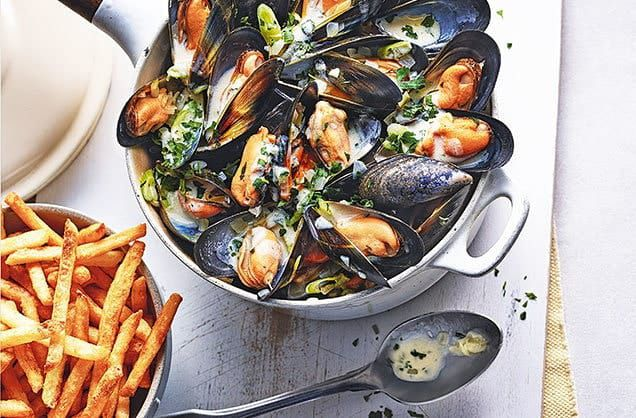 overhead view of steamed mussels in a white pot on a white table with a bowl of fries