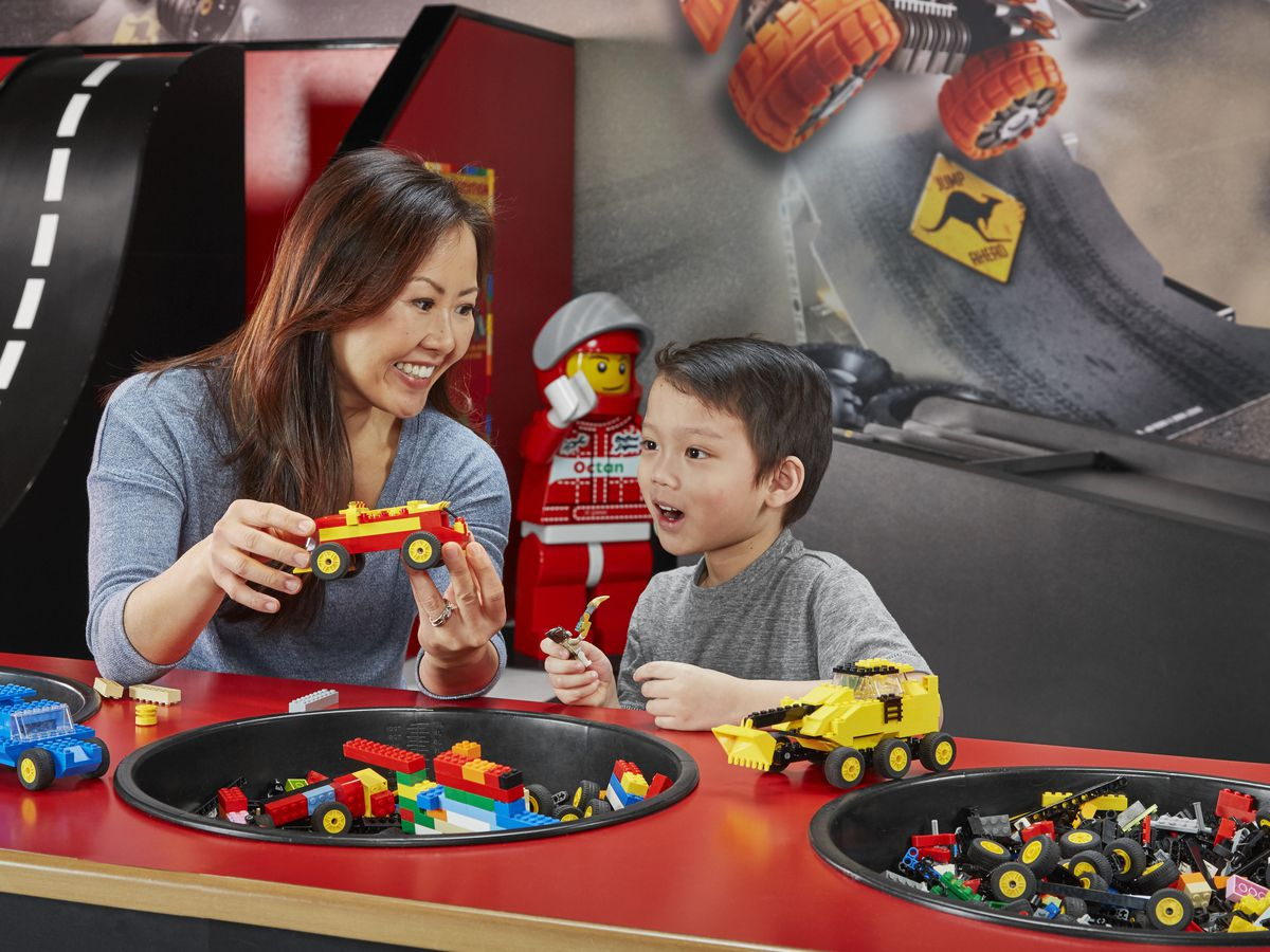 A woman and small child sit at a red table. The woman is holding a toy truck and there are recessed spaces in the table that hold other lego toys.