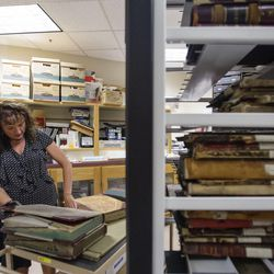 Julie Dole, Salt Lake County chief deputy recorder, shows examples of old books inside the vault of the Salt Lake County Recorder's Office in Salt Lake City on Monday, June 5, 2017.