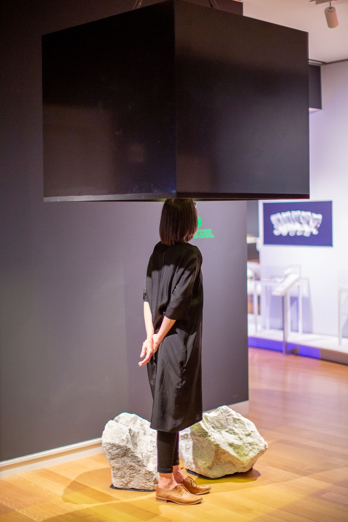 A person stands in a suspended black metal box, which sprays the scent of an extinct flower produced through genetic engineering