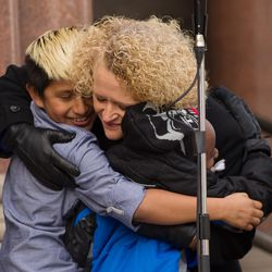 Newly inaugurated Salt Lake City Mayor Jackie Biskupski, center, hugs her fiancÉe's son, Jack Iverson, left, and her son, Archie, following her remarks outside the City-County Building on Monday, Jan. 4, 2016.