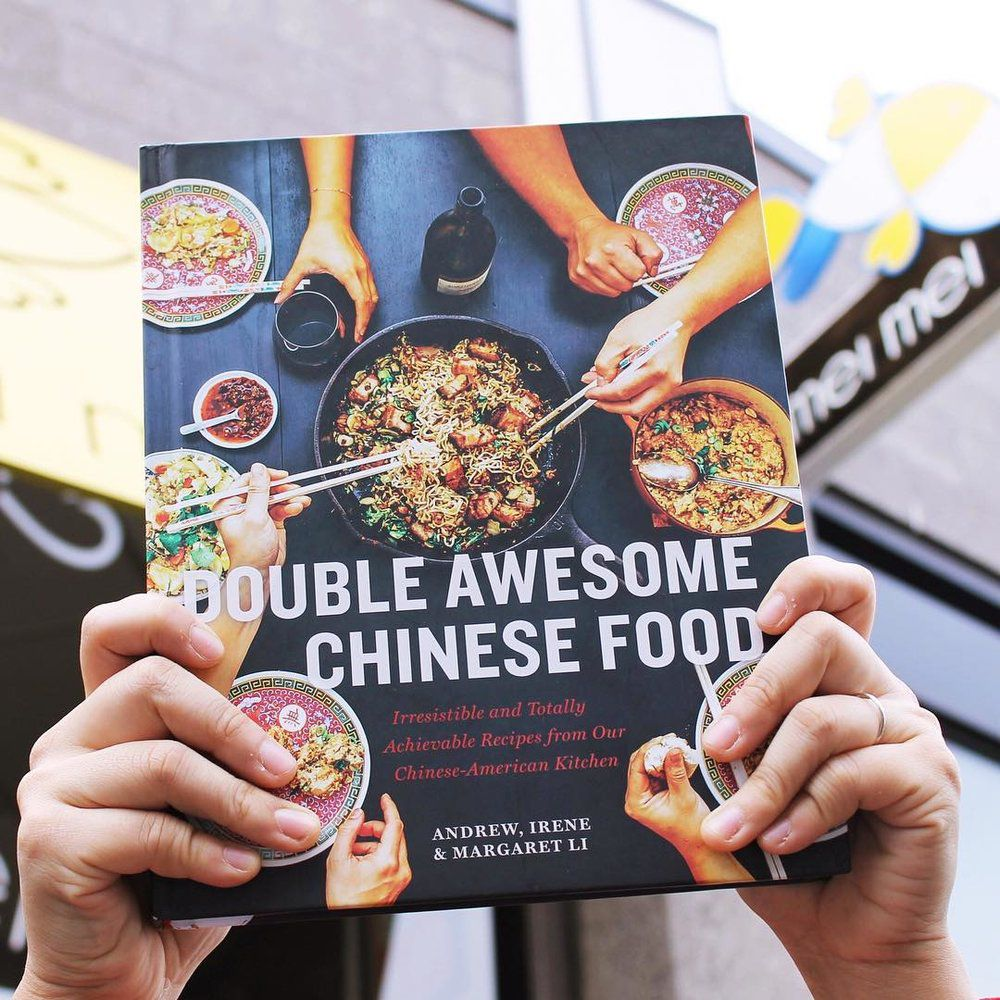 Two hands hold up a cookbook. Signage for the cookbook's namesake restaurant, Mei Mei, is visible in the background.