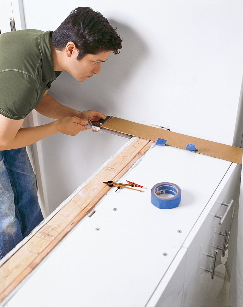 Man Tapes Template Of Butcher Block Countertop In Place