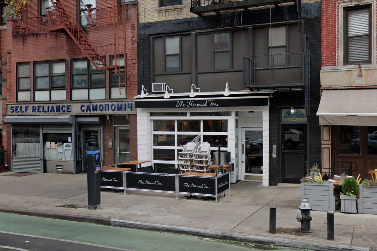 A white and black restaurant storefront with a sidewalk cafe out front and stacked chairs and tables in front of the restaurant
