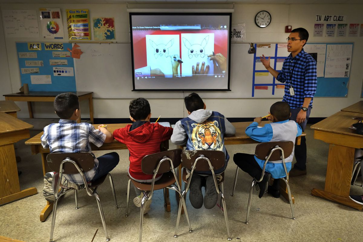 An April 2019 photo shows a teacher next to a smart board talking to four male students sitting at a table and looking at the board.