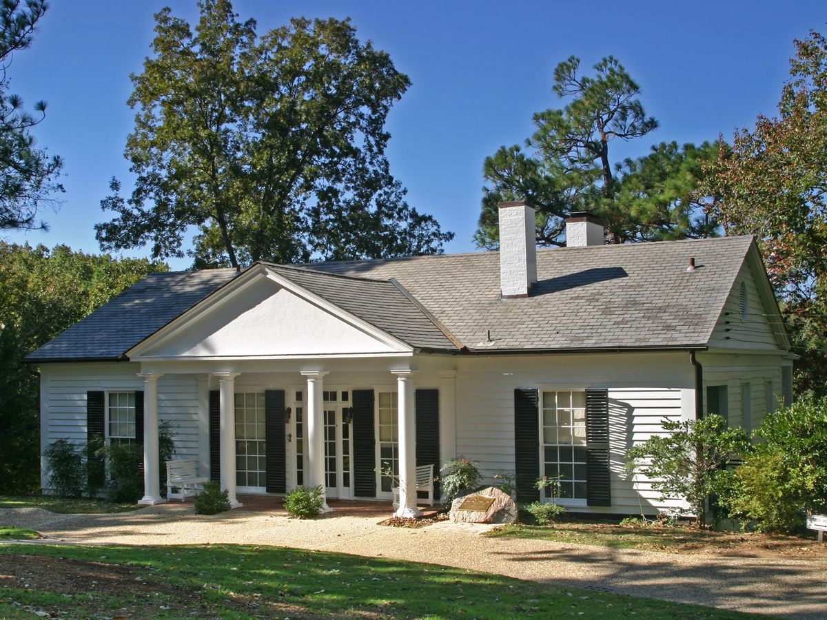 The exterior of Roosevelt's little white house historic site in Atlanta. The facade is white with a grey roof. There are columns near the entrance and a chimney on the roof.