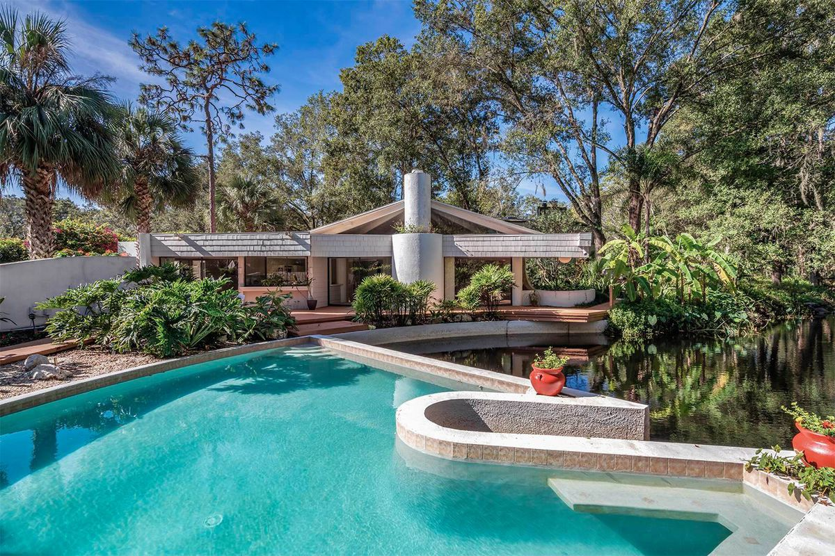 Exterior shot of modern home with vaulted roof and angular pool in front and set beside a lagoon.