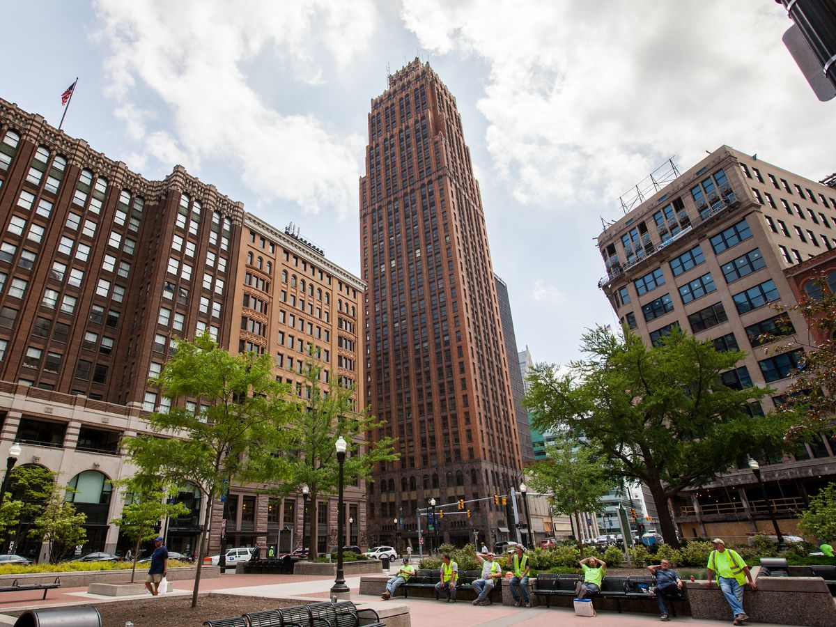 Tall, brick Art Deco skyscraper with a square base that narrows as it gets taller. A row of smaller buildings and a plaza is in the foreground.