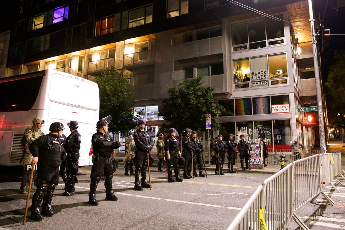 Police stand near a barricade on a Seattle street at night.