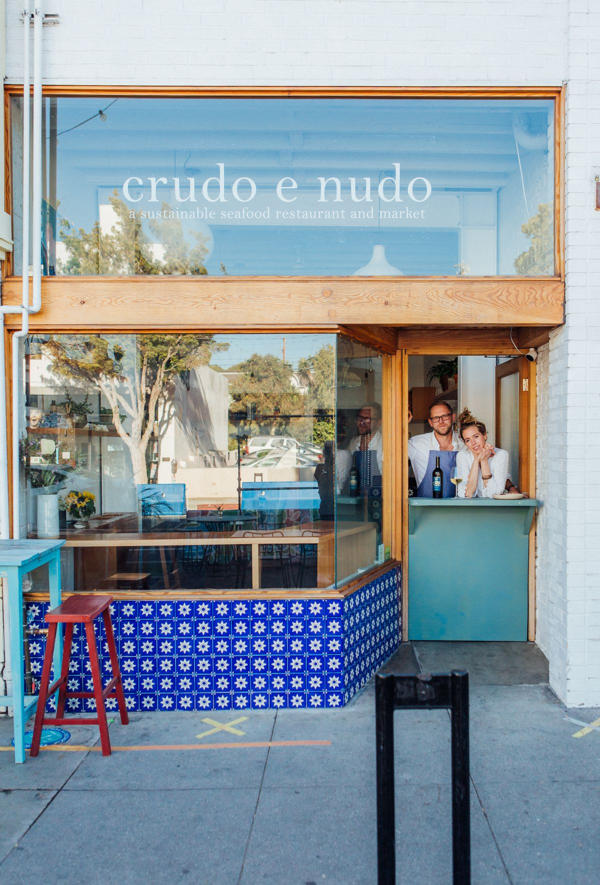 A chef and co-owner stand inside their Dutch door seafood shop.
