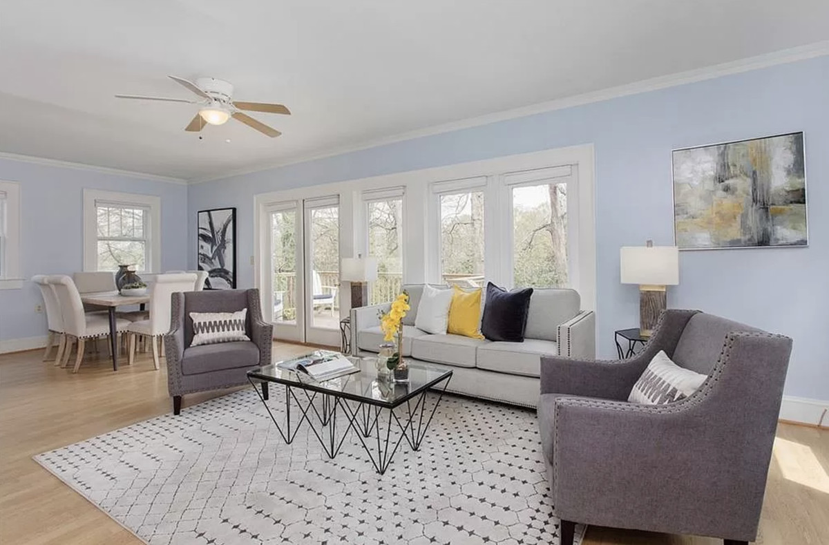 Living room with pastel blue walls, floor-to-ceiling windows overlooking the backyard, couch, chairs, and area rug.