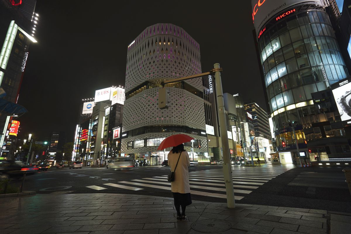 A woman stands at the empty Ginza shopping district in Tokyo.