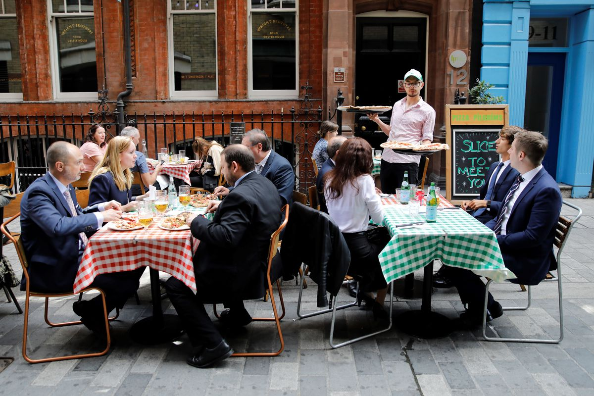 Diners sit outside a London restaurant in the eat out to help out scheme