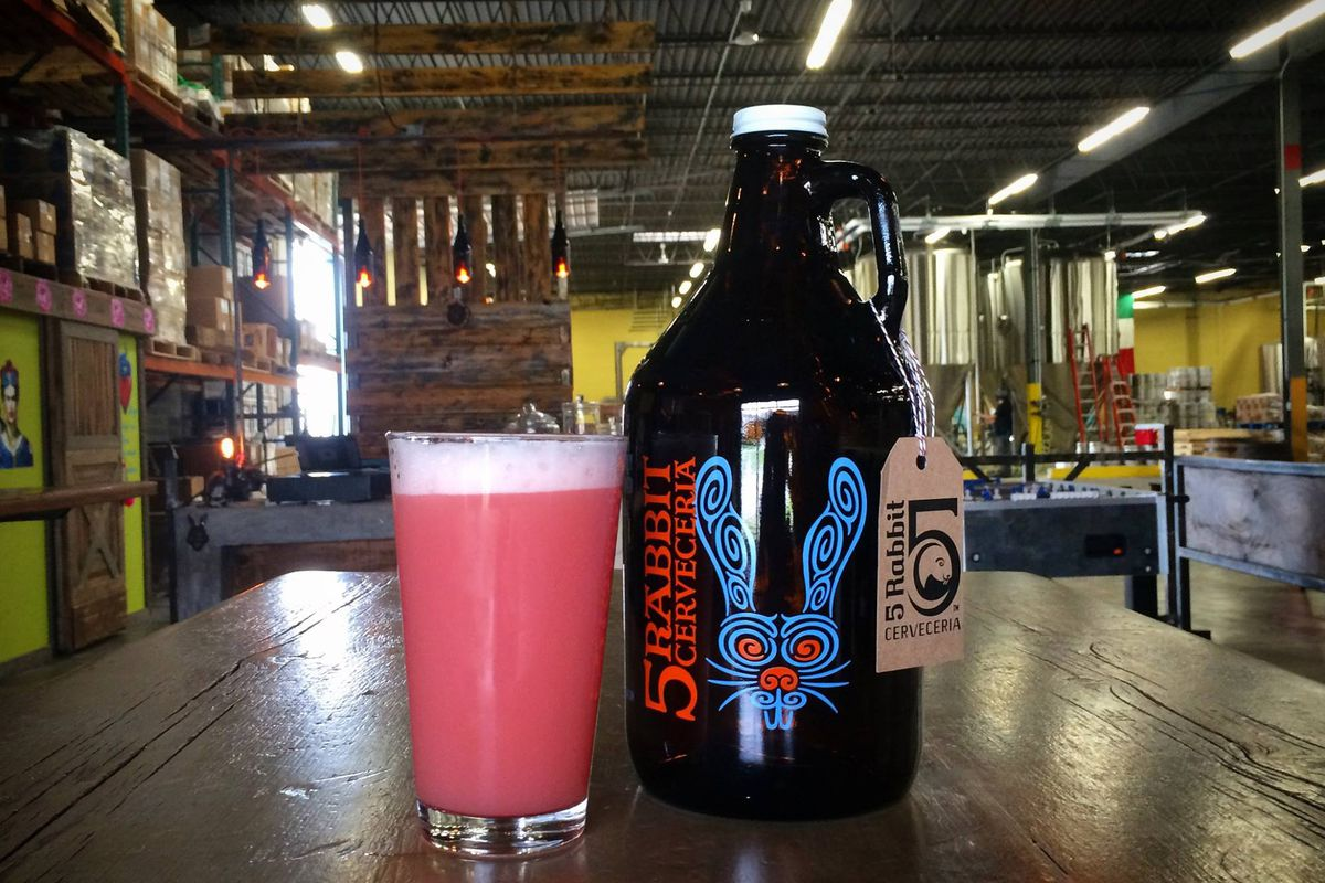 A pink beer in a pint glass next to a beer growler.